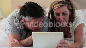 Mature couple lying on bed using a digital tablet