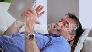 Mature man lying on the sofa using his digital tablet