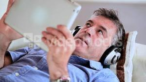 Mature man lying on the sofa using his digital tablet listening to music