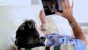 Mature man lying on the couch listening to music and using tablet pc