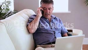 Annoyed man talking on the phone on the sofa with his laptop