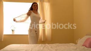 Young woman taking off her shirt in bedroom
