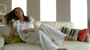 Young woman sitting down on her couch