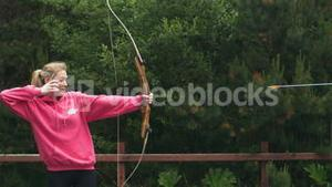 Blonde woman shooting bow and arrow