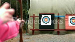 Woman shooting bow and arrow to the target