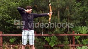 Athletic man shooting a bow and arrow