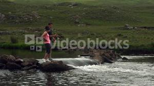 Couple standing on rocks in the middle of a river