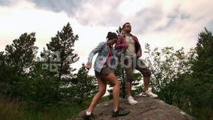 Athletic couple reaching the summit and admiring the view