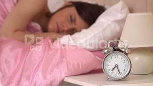 Alarm clock ringing and waking a sleeping woman