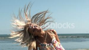 Happy blonde shaking hair on the beach