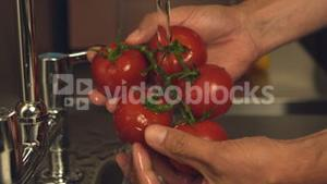 Hands washing tomatoes under water tap