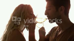 Couple drinking together with crossed arms against sunlight