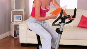 Sporty woman exercising on exercise bike at home