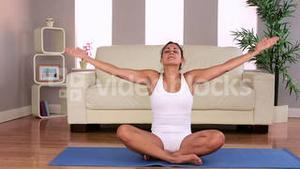 Fit attractive brunette doing yoga exercise in living room