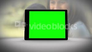 Tablet with green screen in front of family outdoors