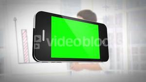 Smartphone with green screen in front of business people working