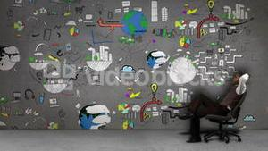 Businessman sitting in front of several animated business processes