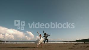 Happy newlywed couple jumping in the air on the beach