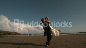 Happy groom spinning his bride on the beach