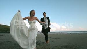 Happy newlywed couple running on the beach