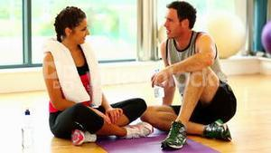 Young sporty friends chatting sitting on floor