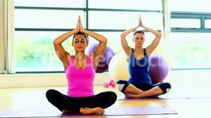 Lovely calm women meditating sitting in lotus position
