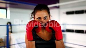 Aggressive fit woman wearing red boxing gloves boxing