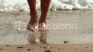 Female feet walking out of water