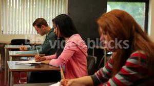 Attentive students sitting in a classroom and taking notes