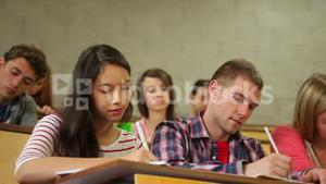 Students listening carefully in lecture hall and taking notes