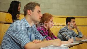 Focused students listening in lecture hall and taking notes
