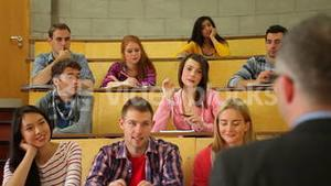 Student raising her hand to ask question in lecture