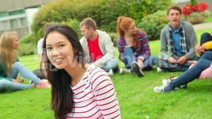 Student smiling at camera with friends behind her on grass