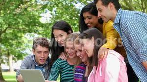 Students looking at the laptop together and laughing