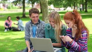 Three students using laptop together and laughing