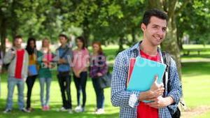 Student smiling at camera with friends standing behind him on grass