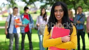 Student smiling at camera with friends standing behind her