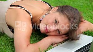Happy student sleeping on grass in front of laptop