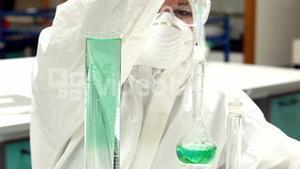 Science student in protective suit working with green chemicals