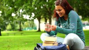 Pretty student sending a text on the grass