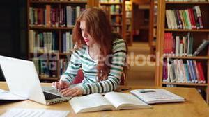 Focused student using laptop in the library