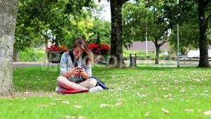 Student sitting on the grass making a phone call