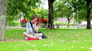 Happy student sitting on the grass making a phone call