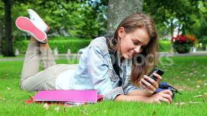 Happy student lying on the grass sending a text