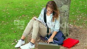 Student studying and leaning against a tree