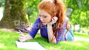 Student lying on the grass making notes