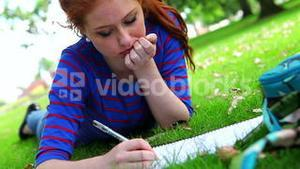 Pretty young student lying on the grass studying