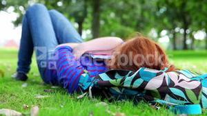 Pretty young student lying on the grass on her bookbag