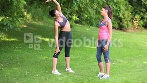 Fit friends stretching during their run