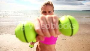 Fit blonde punching with dumbbells